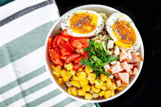 Porridge with vegetables, chicken and egg, top view