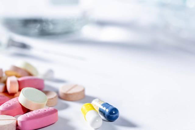 Pillen und Tabletten in verschiedenen Farben und Formen vor weißem Hintergrund