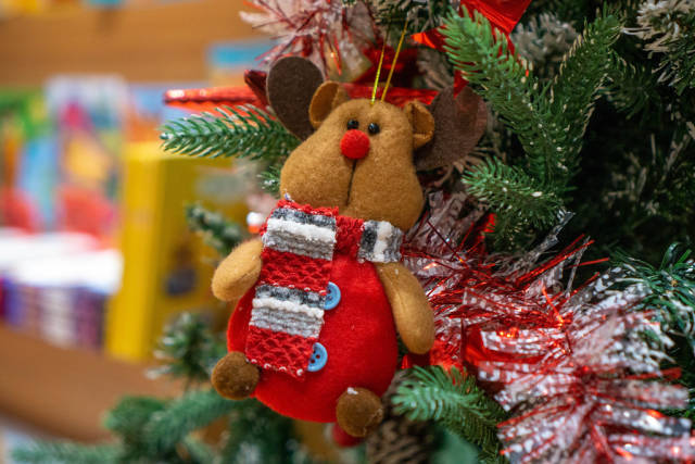 Close Up Bokeh Photo of Stuffed Animal Bear with Scarf on a Christmas Tree as Decoration
