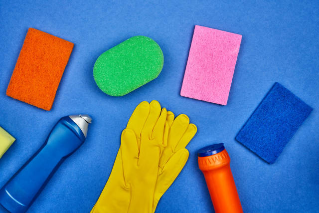 Chemical cleaning supplies bottles and different sponges on blue background