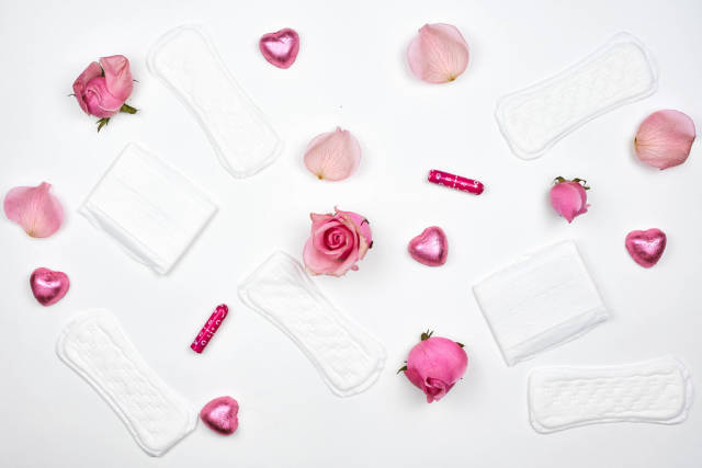 Sanitary pads and tampons with roses on white background
