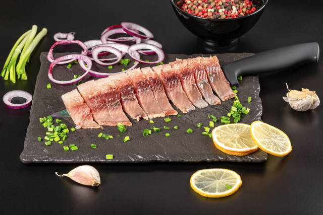 Appetizing pieces of pickled herring with red and purple onions, mix peas and sliced lemon on dark background