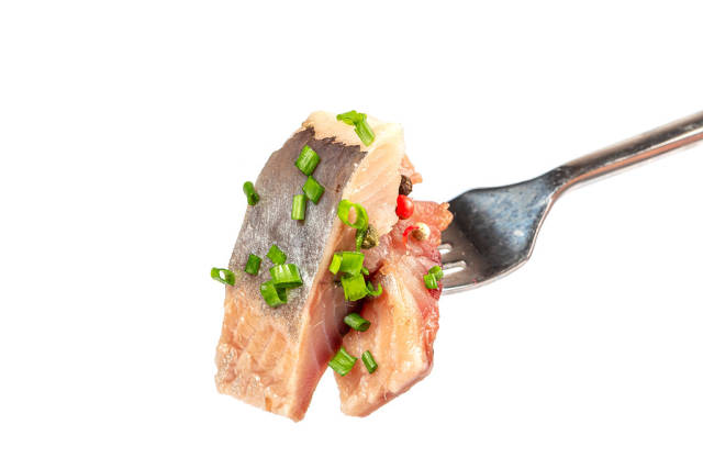 Pieces of salted herring on fork on white background