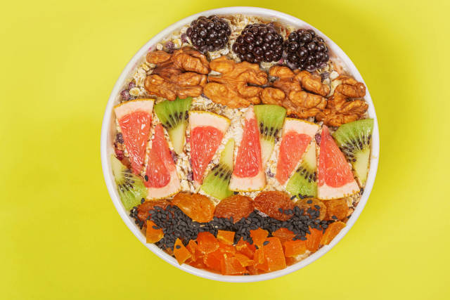 Oatmeal in a white bowl with blackberries, walnuts, grapefruit, kiwi and dried apricots, yellow background, top view