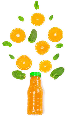Orange juice bottle with mint leaves and orange slices on white, top view