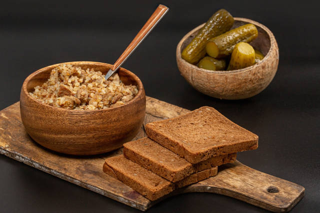 Buckwheat porridge in a wooden bowl on a dark background with pickles and black bread