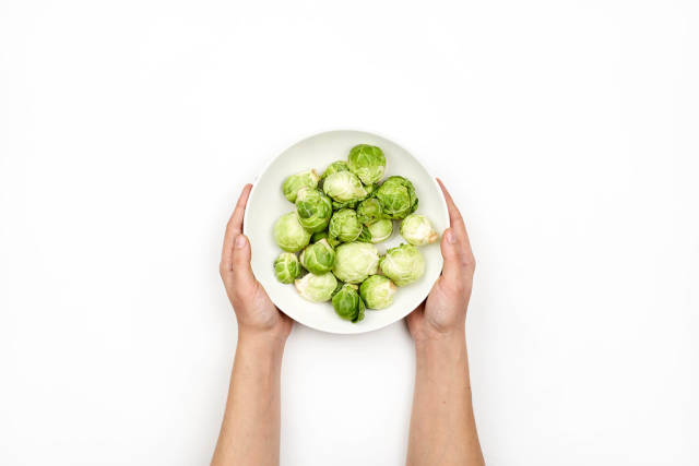 Woman hands holding a bowl of tiny cabbages also called Brussels sprouts