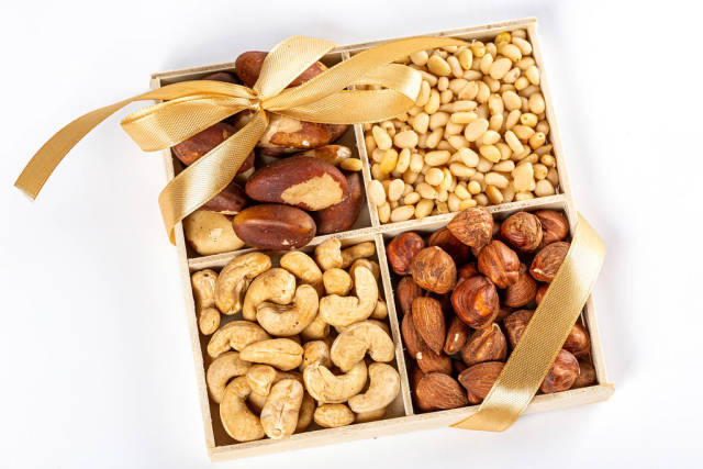 Set of nuts in a box with ribbon and bow on white background