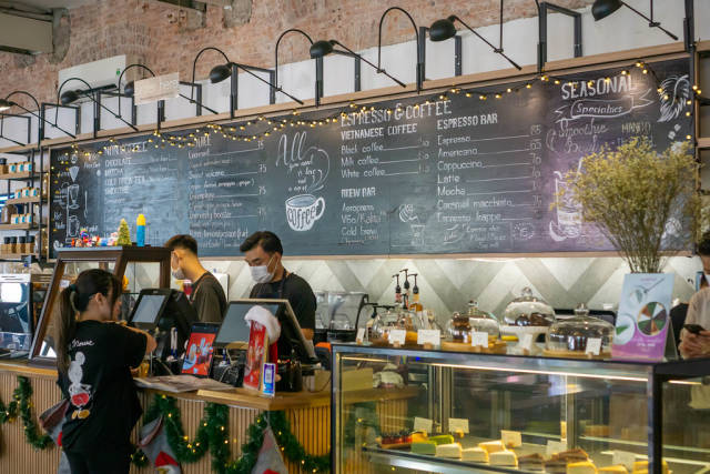 Cafe Staff wearing Facemasks at a Counter with large Menu on a Blackboard decorated with Christmas String Lights