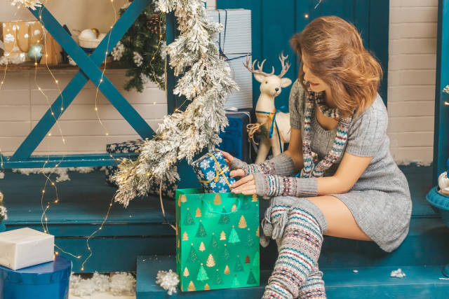 Woman in gray knitted dress with a scarf puts a present in a gift bag
