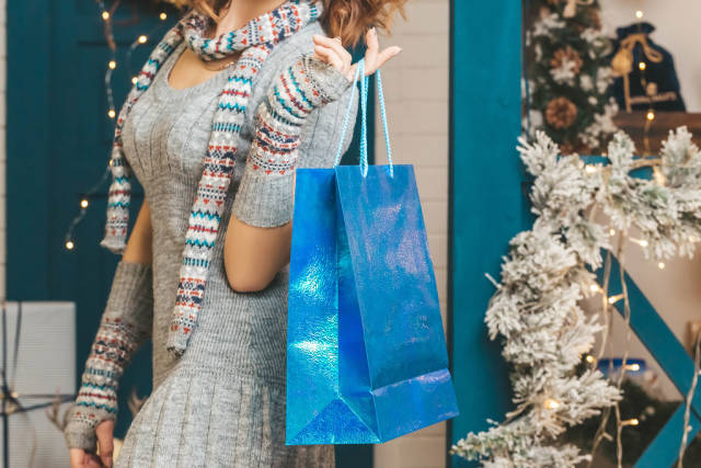 Blue gift bag in female hand, christmas shopping concept