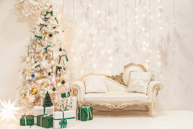 Festive light living room interior with white christmas tree, gifts, sofa and garlands