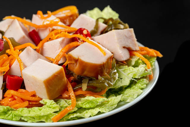 Close-up salad with smoked chicken, carrots, lettuce and seaweed