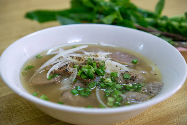 Close Up Food Photo of Vietnamese Noodle Soup Pho Bo with Fresh Herbs in the Background