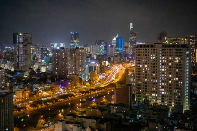 View of Busy Highway in District 1 and City Center with Bitexco Financial Tower at Night in Ho Chi Minh City, Vietnam