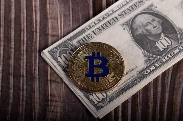 Golden Bitcoin coin on US dollar banknote