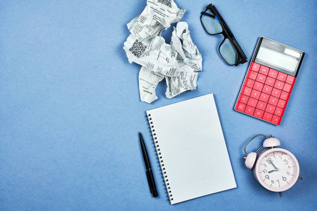 Stack of shop checks, calculator, alarm clock and blank notepad with copy space