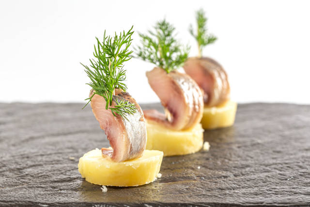 Snack-boats of pickled herring and potatoes