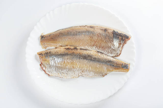 Fillet of pickled herring on a plate, top view