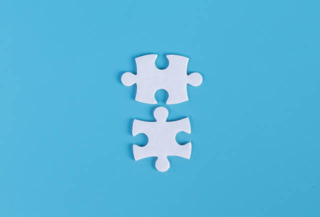 Two pieces of jigsaw puzzle on blue background