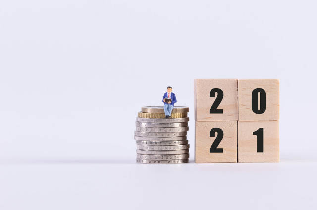 Man sitting on stack of coins and wooden cubes with 2021 text on white background