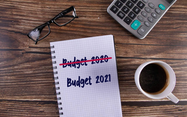 Open notebook with crossed Budget 2020 text and Budget 2021 text on wooden table