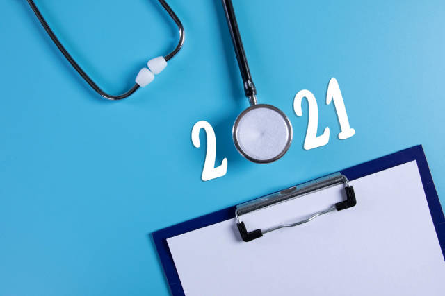 Clipboard and stethoscope with 2021 text on blue background