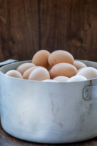 Old pan with chicken eggs on wooden background