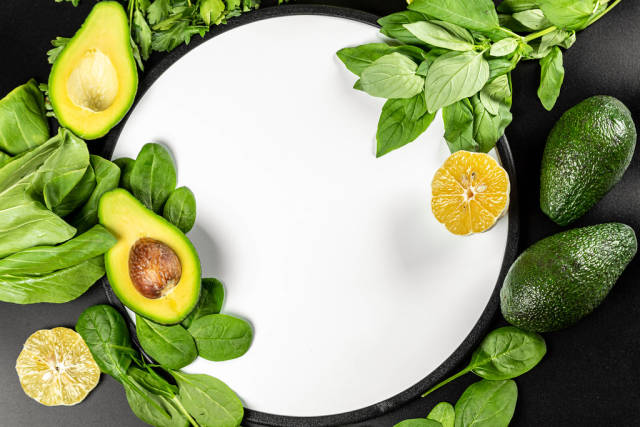 Top view, frame with green vegetables and herbs on black background with white kitchen board in the middle