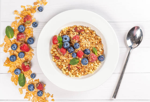 Top view, multigrain breakfast on wooden white background with strawberries, blueberries and mint leaves