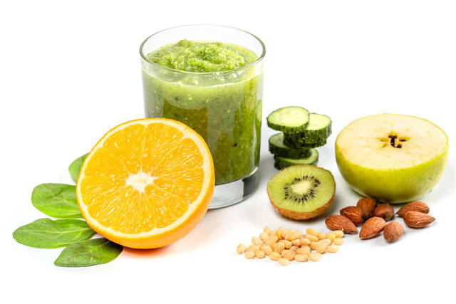 Glass of green smoothie with fresh apple, orange halves, sliced cucumber, spinach leaves, almonds and pine nuts
