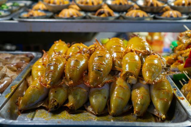 Gegrillter Kalmar und andere Meeresfrüchte bei einer Straßenküche auf einem Nachtmarkt in Vietnam