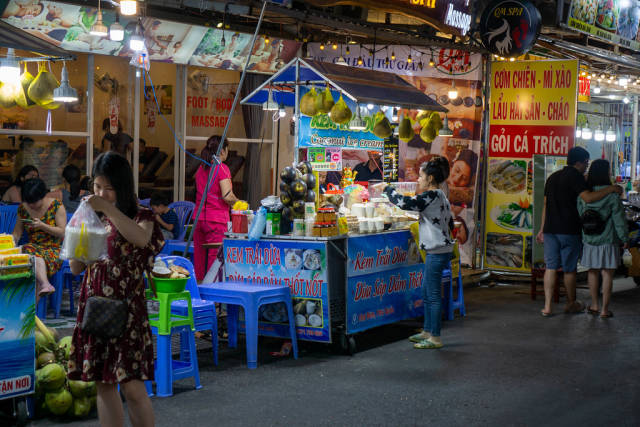 Street Food Vendor selling Coconut Ice Cream, Restaurants and Massage Parlors at the Phu Quoc Night Market in Vietnam