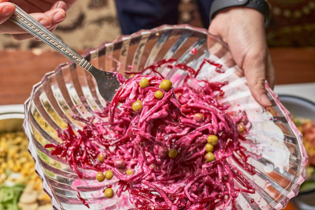Woman holds a plate of healthy beet salad