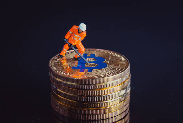 Miner working on a golden Bitcoin