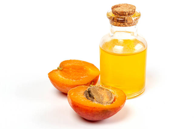 Halves of a ripe apricot and a bottle of oil on a white background