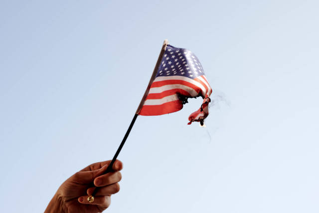 Hand holding burning the American flag - a symbol of mass protests in the USA