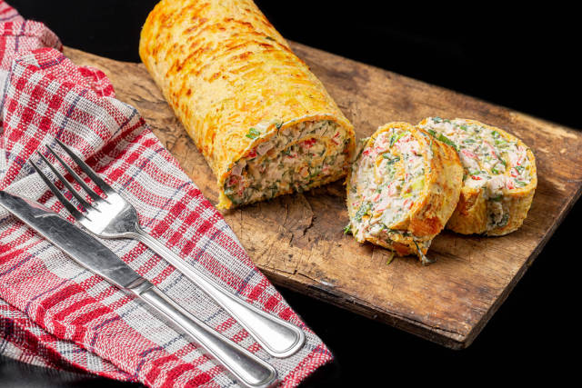 Cheese and egg roll with crab sticks and herbs on an old kitchen board