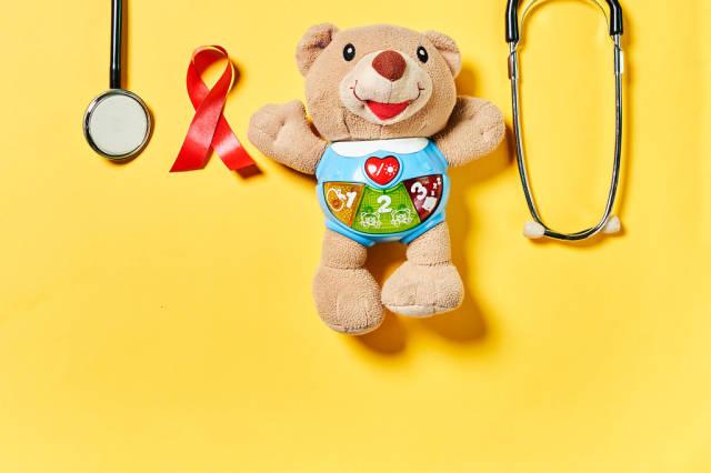 Weltkrebstag - 4. Februar: rote Schleife, medizinische Ausrüstung, Kuscheltier vor gelbem Hintergrund