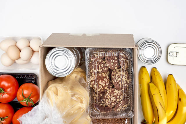 Survival food kit with cookies, tagliatelle noodles, tomatoes, bananas, eggs and tin cans in a box