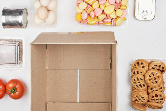 Top view of an empty cardboard box surrounded by food products: tomatoes, eggs, sweets, tin cans