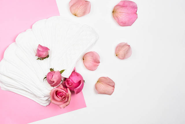 Frauen-Hygieneartikel: lose Slipeinlagen und Rosen auf rosa-weißem Hintergrund mit Platz für Text