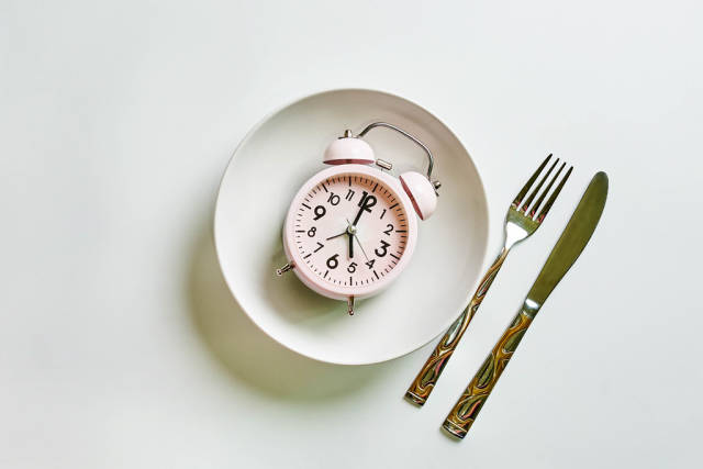 Alarm clock on plate, spoon and fork on white background