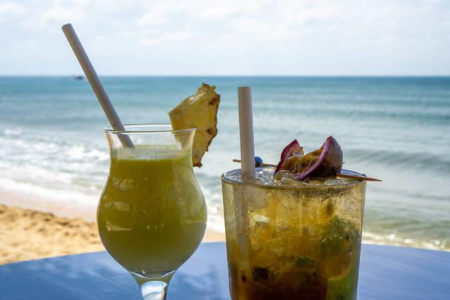 Pina Colada mit frischer Ananas und Mojito mit Passionsfrucht, Eiswürfeln und Minze in Cocktailgläsern in einer Strandbar mit Meerblick in Phu Quoc, Vietnam