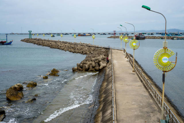Sea Walkway with Street Lights and Tetrapod Structures at Phu Quoc Harbour with Fishing Boats and Mountains in the Background in Vietnam