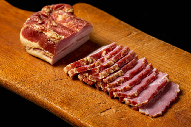 Delicious homemade smoked bacon on a cutting board