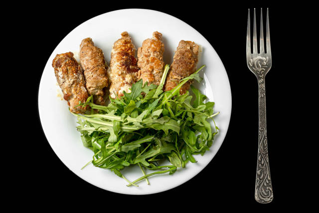 Baked meat rolls stuffed with cheese and arugula, top view