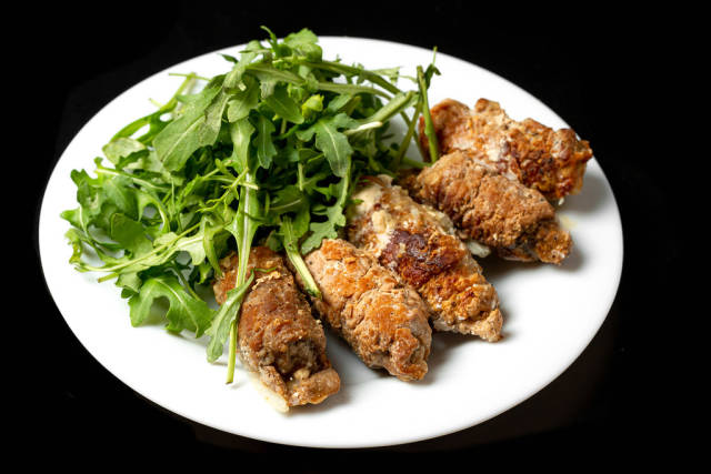 Meat rolls with fresh arugula leaves, close-up