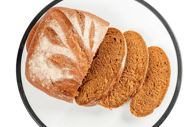 Slices of fresh rye bread on white background, top view