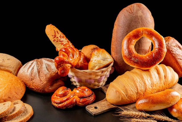 Assortment of fresh assorted baked breads and buns on black background with spikelets